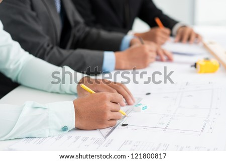 Close-up image of architects being occupied with paperwork - stock photo