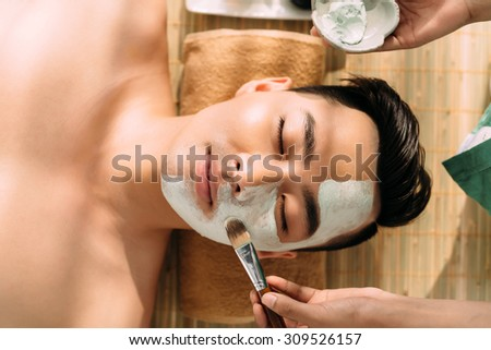 Close-up image of beautician applying clay mask to the face of young man - stock photo