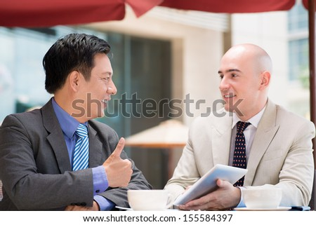 Close-up image of business partners, one of them thumbing up in the sign of agreement - stock photo