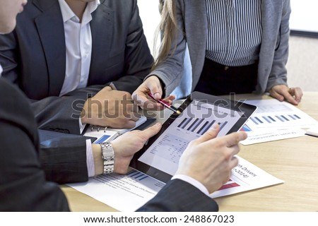 Close up image of business team discussing the data Female explains the data to her male counterpart, pointing on the chart on the screen of tablet PC - stock photo