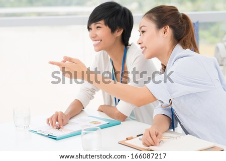 Close-up image of businesswomen at the seminar where one of them pointing at something on the foreground - stock photo