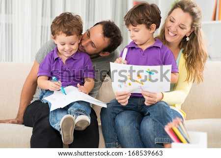 Close up image of cheerful parents drawing with their children at home  - stock photo