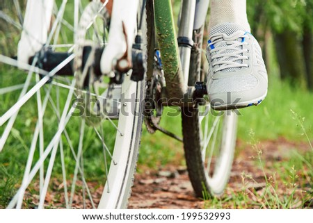 Close-up image of cyclist man feet riding mountain bike on trail in summer - stock photo