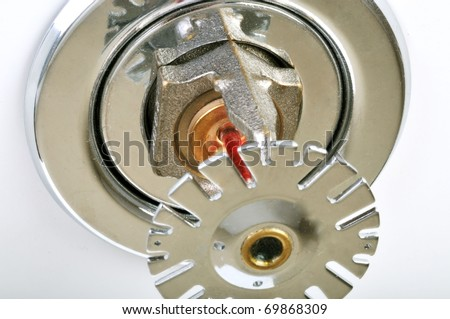 Close up image of fire sprinkler on white. Fire sprinklers are part of an integrated water piping system designed for life and fire safety. - stock photo
