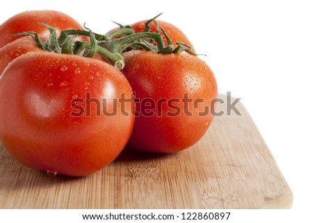 Close up image of fresh tomato in wooden plate against white background - stock photo