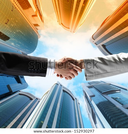 Close up image of hand shake against skyscrapers - stock photo