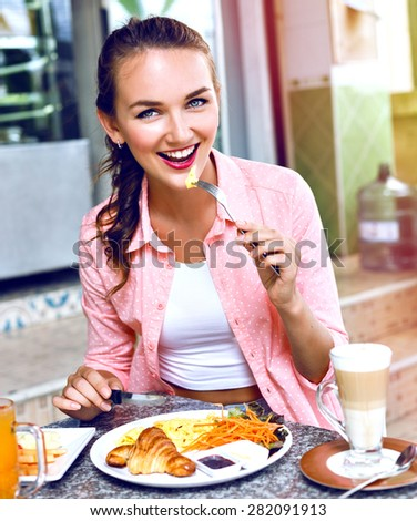 Close up image of happy smiling woman enjoy her morning french breakfast on open cafe terrace, tasty organic food. - stock photo