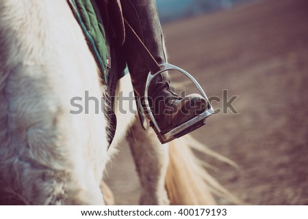 Close up image of horse riding boots and white horse - stock photo
