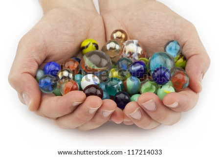 Close-up image of human hand full of colorful round marbles isolated on a white background - stock photo