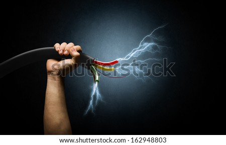 Close up image of human hand holding cable - stock photo