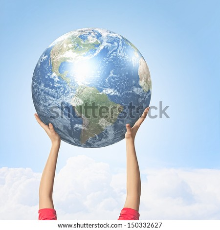 Close -up image of human hands holding globe. Elements of this image are furnished by NASA - stock photo