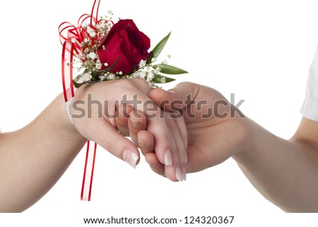 Close-up image of lady's wrist with red rose corsage over the white background - stock photo