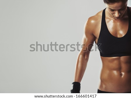Close up image of middle eastern female in sports clothing relaxing after workout on grey background. Muscular female body with sweat. Image with copyspace for text - stock photo