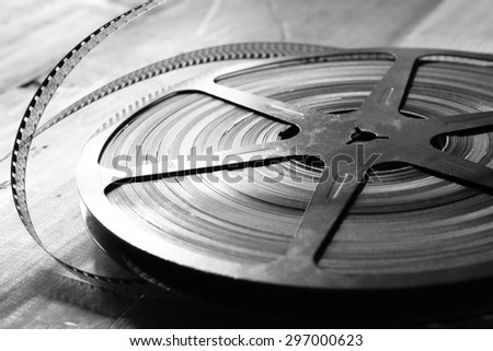 close up  image of old 8 mm movie reel over wooden background. black and white photo   - stock photo