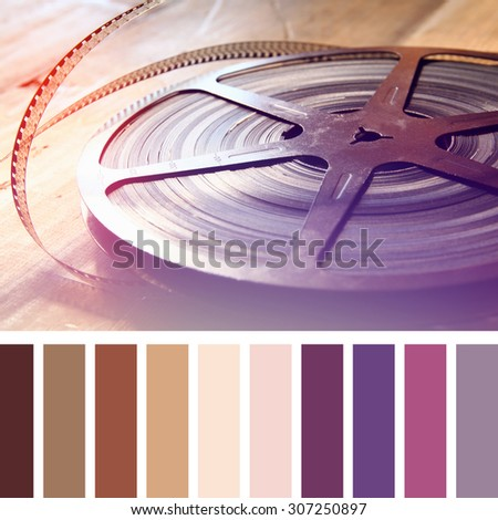 close up image of old 8 mm movie reel over wooden background. vintage filter with palette color swatches  - stock photo
