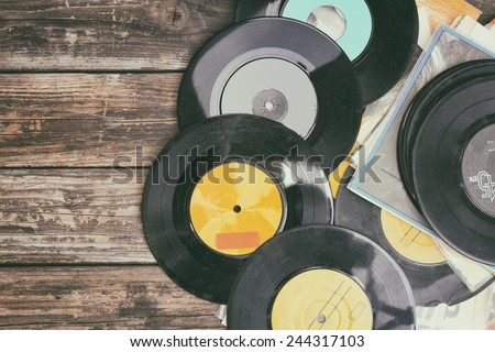 close up image of old records over wooden table , image is retro filtered .  - stock photo