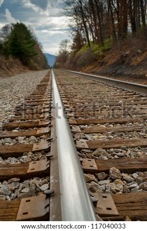 Close up image of railroad from a low perspective seeing the rail and the distance on the track in North Carolina - stock photo