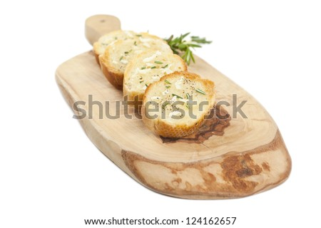 Close up image of slices of baguette bread with garlic spread and pepper on wooden board - stock photo