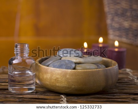 Close-up image of spa massage stones with a bottle of essential oil and lighted candle - stock photo