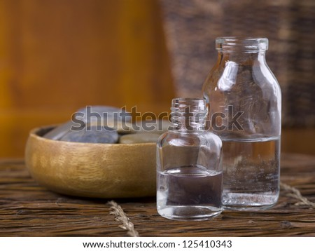 Close-up image of spa massage stones with essential oil on the wooden table - stock photo