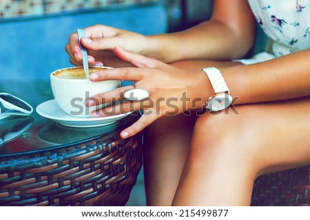Close up image of tan stylish woman shaking her morning coffee, wearing summer trendy dress and accessorizes , siring alone at cafe. Bright colors. - stock photo