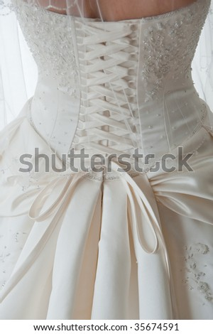 Close-up image of the detailed laces on the back of a wedding dress - stock photo