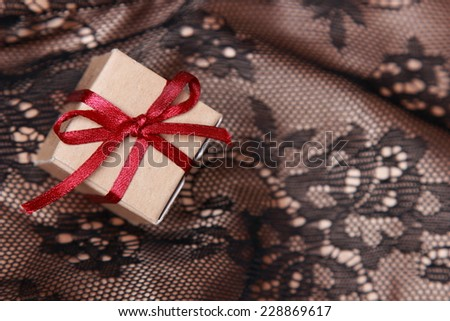 Close up image of tiny vintage gift box over Black and golden fabric with ornament pattern background on holiday theme - stock photo