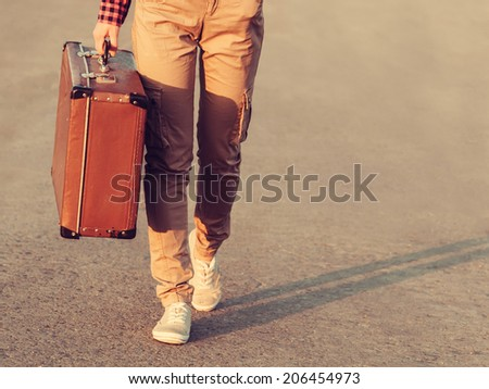 Close-up image of traveler legs goings, vintage suitcase, travel theme. With retro filter - stock photo