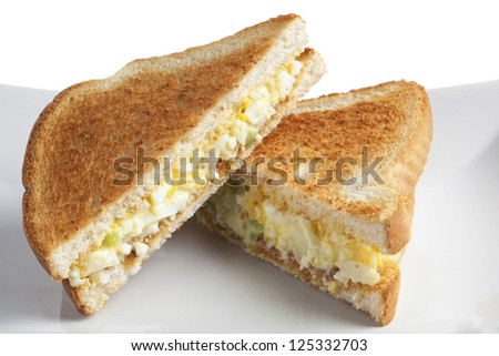 Close up image of two slices of egg salad sandwich against white background - stock photo