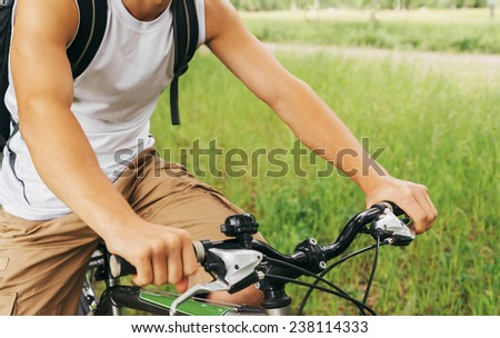 Close-up image of unrecognizable cyclist man's hands holding handlebar of mountain bike in summer park - stock photo