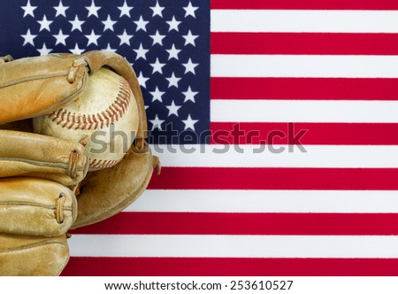 Close up image of worn leather mitt and used baseball with United States of America flag in background. Concept of baseball sport in America. - stock photo