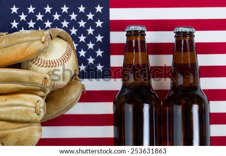 Close up image of worn leather mitt, used baseball and full beer bottles with United States of America flag in background.  - stock photo