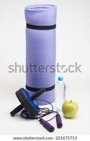 Close up image of yoga mat with skipping rope, water bottle, workout fitness exercise roller and apple closeup isolated on white background - stock photo