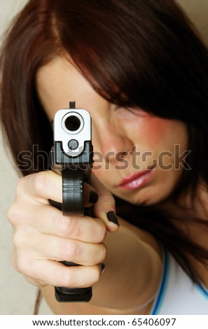 Close-up image of young attractive female pointing gun.  Focus is on barrel of gun. - stock photo