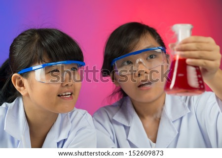 Close-up image of young chemists testing red liquid in the lab - stock photo