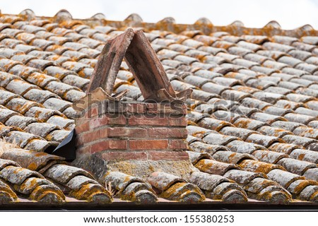 Close up image on very old roof tiles background with chimney - stock photo