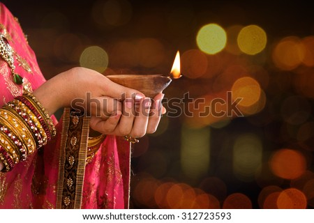 Close up Indian woman in traditional sari lighting oil lamp and celebrating Diwali or deepavali, fesitval of lights at temple. Female hands holding oil lamp, beautiful lights bokeh background. - stock photo