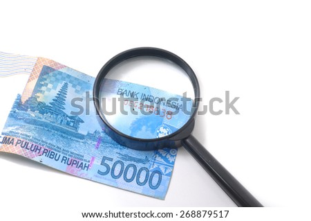 Close up Indonesian currency using magnifying glass on white background. - stock photo