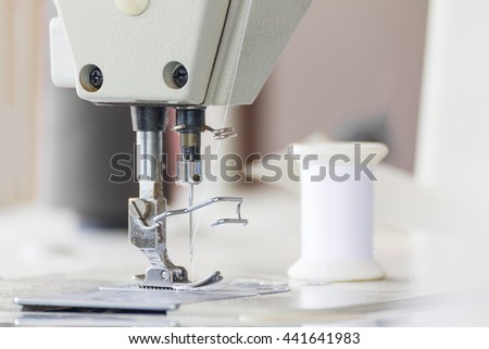 Close up industrial sewing machine in textile factory - stock photo