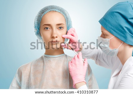 Close up isolated view of doctor in sterile gloves making Botox facial injection in woman's cheek. Young Caucasian female having treatment cosmetic in beauty clinic. Aesthetic medicine, cosmetology  - stock photo