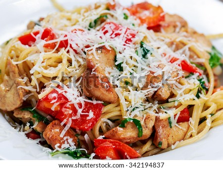 Close up Italian Chicken Breast Pasta spaghetti with red pepper, Parmesan cheese and wild rocket  lives - stock photo