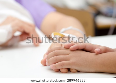 close up kid hands touch mom Hands of patients in hospital - stock photo