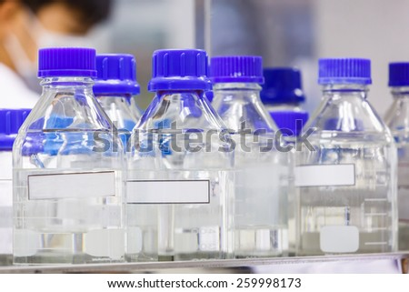 Close up laboratory glass bottle with blue color cap on shelf - stock photo