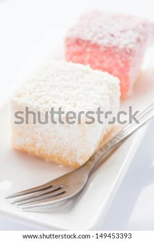 Close up lamington sponge cakes and fork, stock photo - stock photo
