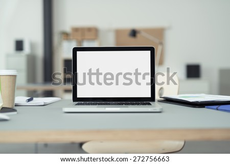 Close up Laptop Computer on Top of Office Table of a Businessman with Empty White Screen, Emphasizing Copy Space. - stock photo