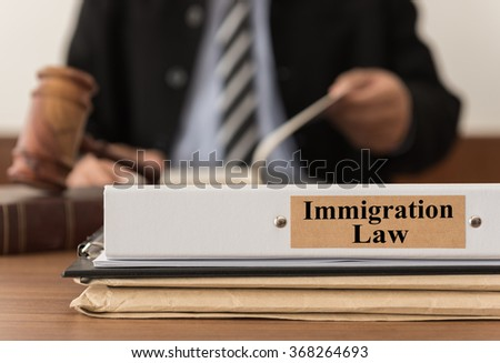 close up lawsuit folder of immigration law with the judge is considering a lawsuit in background. concept of immigration law. - stock photo