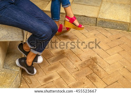 Close up leg  two Woman jeans and sneaker shoes sitting on stone chair outdoor  - stock photo
