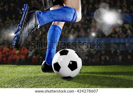 close up legs and feet of football player in action wearing blue socks and black shoes running and dribbling with the ball playing match on green grass pitch at  soccer stadium with flashes and flares - stock photo