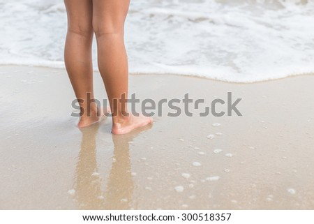 Close up legs of children stand on the beach - stock photo