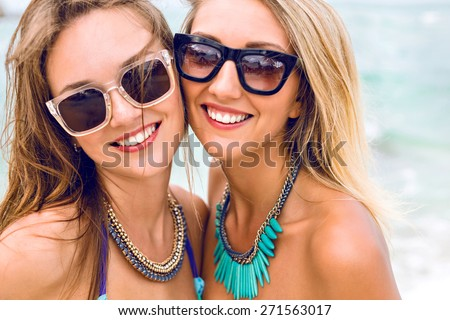 Close up lifestyle fashion portrait of two pretty fresh young brunette and blonde best friends girls, having vacation on the tropical island beach, wearing bikini sunglasses and bright jewelry . - stock photo